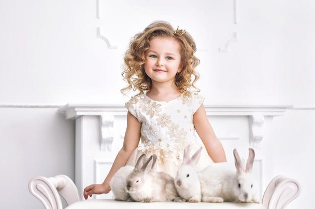 Kleines schönes und süßes mädchen in einem modischen festlichen kleid mit tierkaninchen