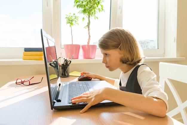 Kleines schulmädchen benutzt den computer, der zu hause an einem schreibtisch sitzt