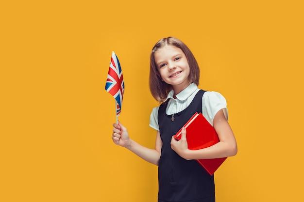 Kleines schulmädchen, das flagge des vereinigten königreichs hält und englisch auf gelbem hintergrund lernt