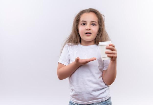Kleines schulmädchen, das weißes t-shirt hält, das tasse kaffee auf isolierter weißer wand hält