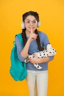 Kleines schulmädchen des mädchens. modernes schulmädchen-alltag. privatschule. vielfältige lernumgebungen, die auf die bedürfnisse zugeschnitten sind. teenager mit rucksack. nettes lächelndes schulmädchen trägt stofftierhund.