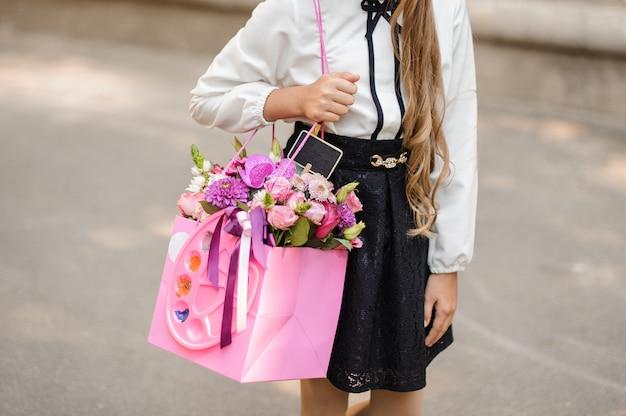 Kleines schulmädchen gekleidet in schuluniform, die einen hellen rosa festlichen blumenstrauß hält