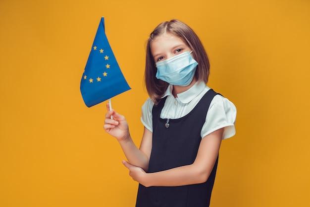 Kleines schulmädchen in schützender gesichtsmaske, das eine flagge des sicherheitskonzepts der europäischen union hält