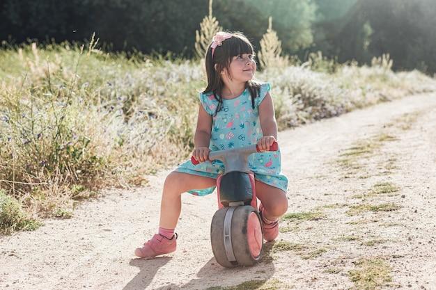 Kleines schwarzes haarmädchen, das ein motorrad auf einer unbefestigten straße reitet