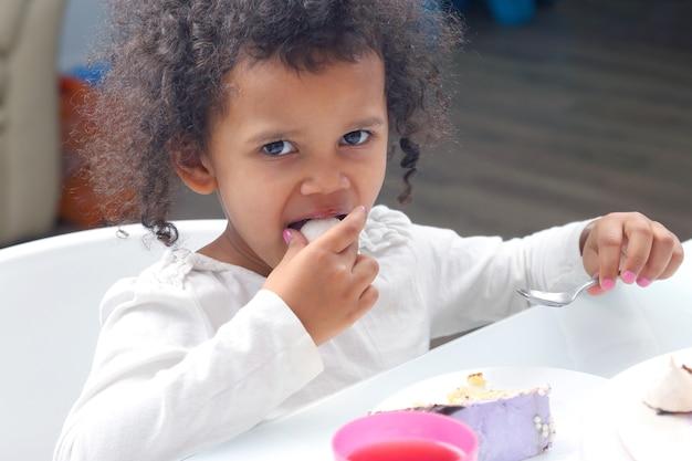 Kleines schwarzes lächelnmädchen, das einen kuchen isst dessertessen