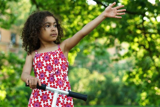 Kleines schwarzes mädchen mit einem tretroller in einem stadtpark