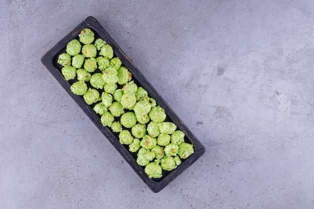 Kleines schwarzes tablett gefüllt mit einer handvoll popcorn-süßigkeiten auf marmorhintergrund. foto in hoher qualität
