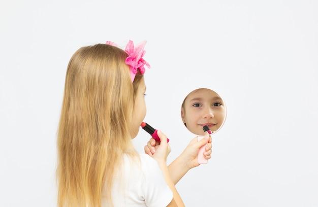 Kleines sechsjähriges mädchen, das mamas lippenstift probiert - lernt, eine moderne frau zu sein