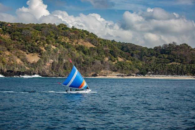 Kleines segelboot schwimmt auf dem wasser mit herrlichem bergblick.