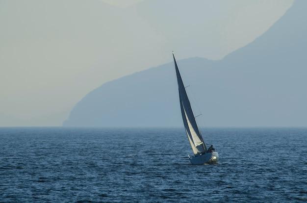 Kleines segelschiff auf dem meer, umgeben von bergen, die tagsüber im nebel liegen