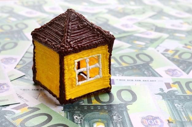 Kleines spielzeughaus liegt auf einer reihe grüner währungsbezeichnungen von 100 euro
