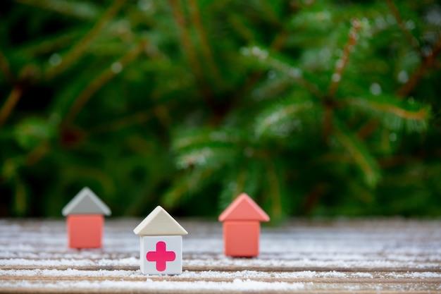 Kleines spielzeughaus mit medizinischem rotem kreuz auf einem schneetisch