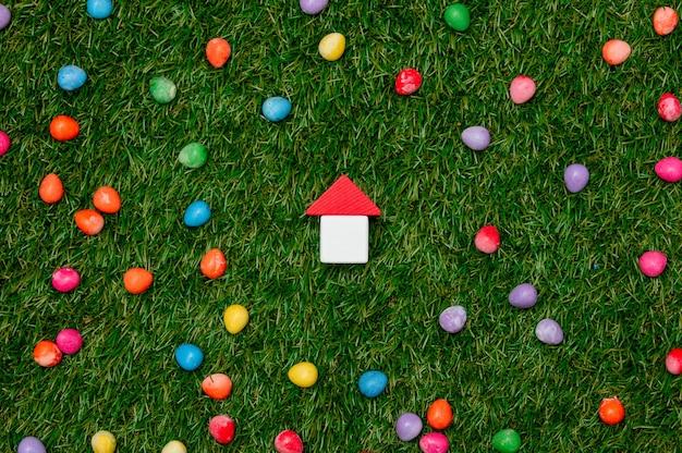 Kleines spielzeughaus und ostersüßigkeiten herum auf grünem gras