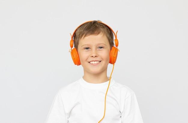 Kleines sportliches jungenkind in sportkleidung, das kopfhörer trägt, musik hört und mit geschlossenen augen auf weißem hintergrund steht. sport, aktives lifestyle-konzept. horizontale aufnahme
