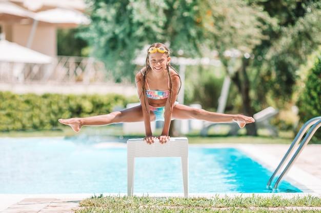 Kleines sportliches mädchen, das spaß swimmingpool im im freien hat