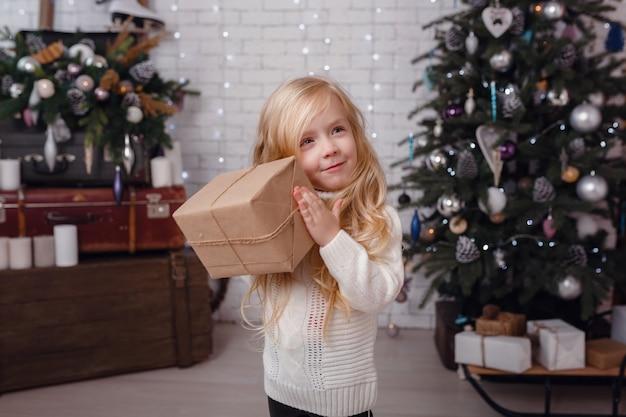 Kleines stilvolles mädchen, das nahe dem neujahrsbaum in erwartung von weihnachten aufwirft.