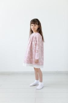 Kleines stolzes brünettes mädchen in einem rosa kleid steht auf einer weißen oberfläche