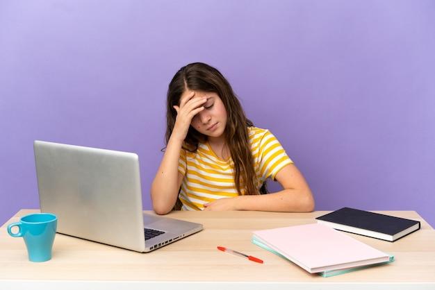 Kleines studentenmädchen an einem arbeitsplatz mit einem laptop auf violettem hintergrund mit kopfschmerzen with