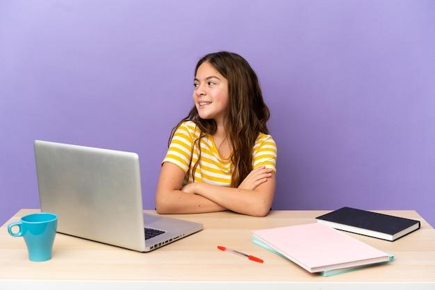 Kleines studentenmädchen an einem arbeitsplatz mit einem laptop auf violettem hintergrund mit verschränkten und glücklichen armen