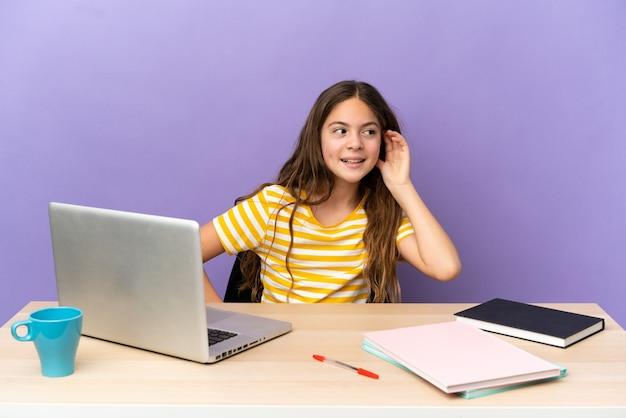 Kleines studentenmädchen an einem arbeitsplatz mit einem laptop, der auf violettem hintergrund isoliert ist und etwas hört, indem er die hand auf das ohr legt