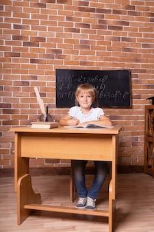 Kleines studentenmädchen, das an einer schulbank sitzt und mathe studiert
