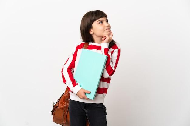Kleines studentenmädchen lokalisiert auf weißem hintergrund, der eine idee beim nachschlagen denkt