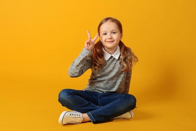 Kleines studentenmädchen sitzt auf dem boden und zeigt ein siegeszeichen.