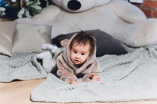 Kleines süßes baby im anzug mit bären im boden.