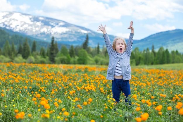 Kleines süßes baby ist schön und glücklich und lächelt im sommer auf der wiese gegen die berge mit schnee