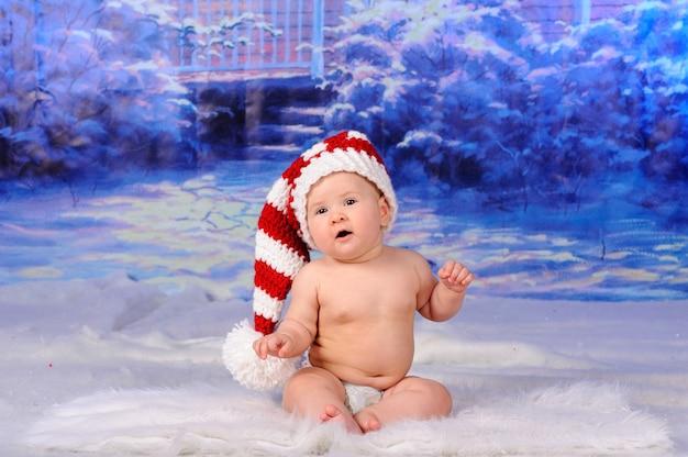 Kleines süßes baby sitzt im schnee in einer weihnachtsmütze.