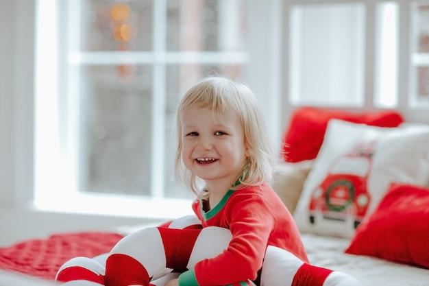 Kleines süßes blondes mädchen im roten weihnachtspyjama, der auf einem bett sitzt