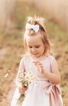 Kleines süßes blondes mädchen mit einem strauß wildblumen in der natur im sommer