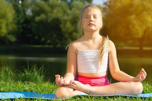 Kleines süßes kaukasisches mädchen, das yoga-pose auf matte im park, gesundheits- und bewegungskonzept praktiziert