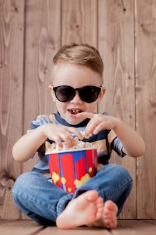 Kleines süßes kind baby 2-3 jahre alt, 3d imax kino brille hält eimer für popcorn, essen fast food auf holz hintergrund. lifestyle-konzept der kinderkindheit.
