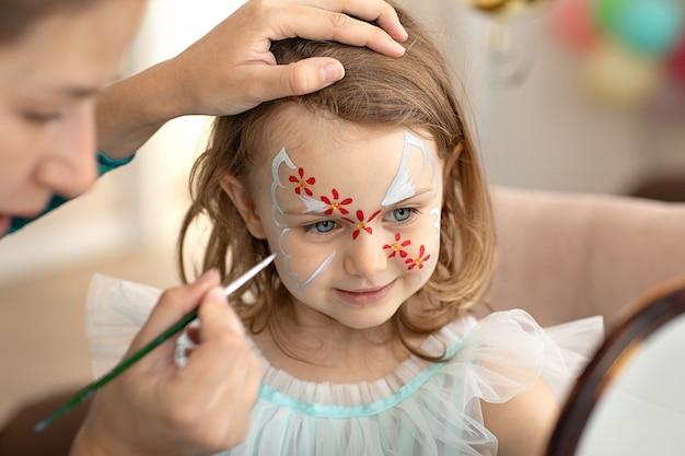 Kleines süßes kind mit gesichtskunst auf geburtstagsfeier gesichtskunstmalereihalloween-party alles gute zum geburtstag