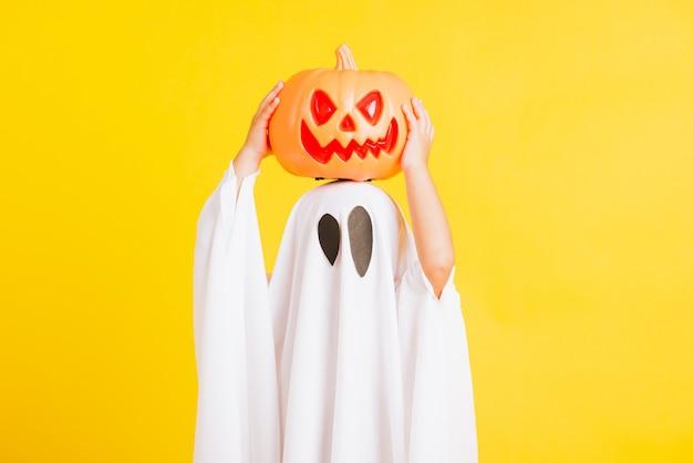 Kleines süßes kind mit weiß gekleidetem kostüm halloween-geist beängstigend hält er orange kürbisgeist auf der hand