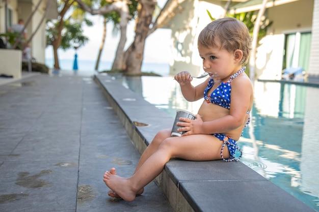 Kleines süßes kleinkind mädchen im badeanzug isst joghurt am pool sitzen. nahaufnahme, weichzeichner