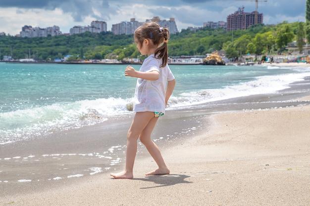 Kleines süßes mädchen an einem sonnigen tag am strand am meer.