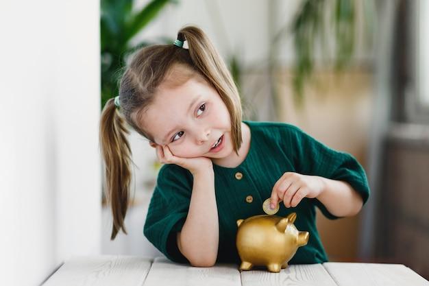 Kleines süßes mädchen, das am tisch drinnen geld in goldsparschwein steckt