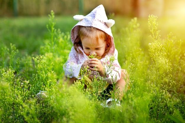 Kleines süßes mädchen, das auf dem feld des grases spielt