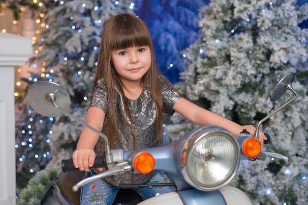 Kleines süßes mädchen, das auf einem motorrad in weihnachten sitzt