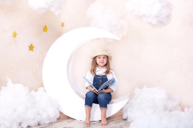 Kleines süßes mädchen, das auf mond mit wolken und sternen sitzt. kind lernt lesen. kleines mädchen liest mit einem buch in den händen. kind träumt. kind lernt und spielt in seinem kinderzimmer. schule