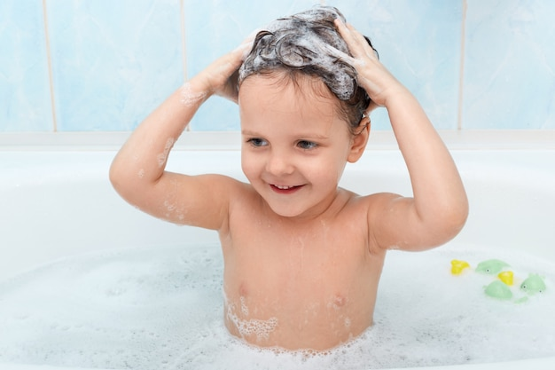 Kleines süßes mädchen, das bad nimmt und ihre haare mit shampoo wäscht