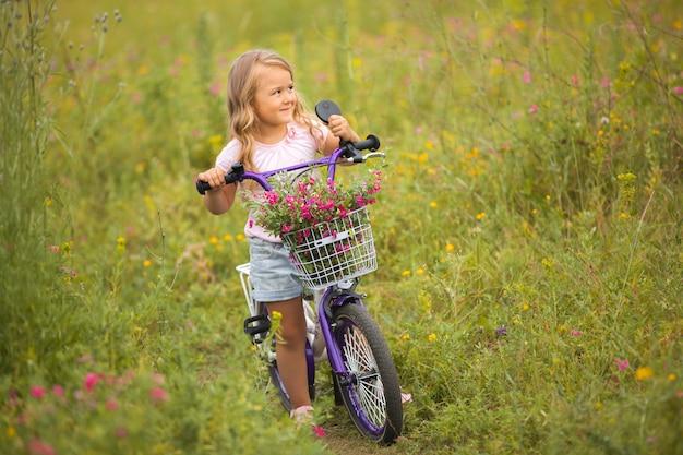 Kleines süßes mädchen, das ein fahrrad mit korb voller blumen reitet. fröhliches kind