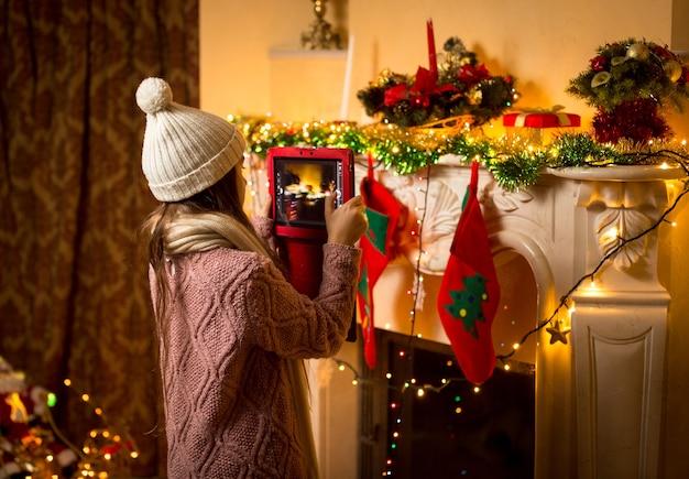 Kleines süßes mädchen, das ein foto von einem dekorierten weihnachtskamin auf einem digitalen tablet macht