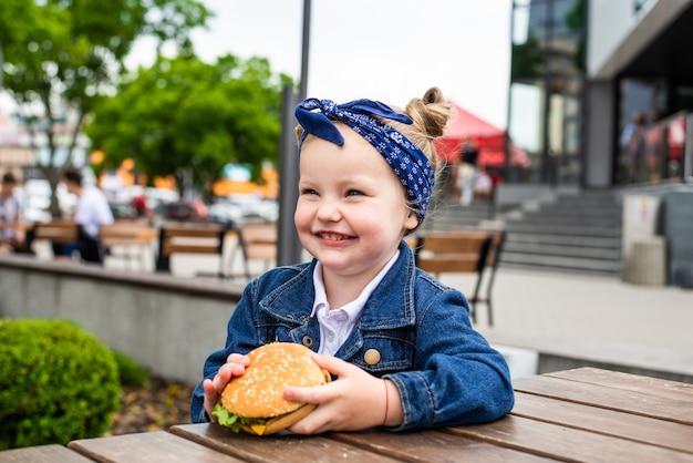 Kleines süßes mädchen, das einen burger in einem café isst. konzept eines fast-food-essens für kinder
