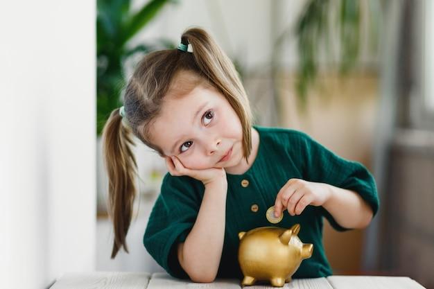 Kleines süßes mädchen, das geld in goldsparschwein am tisch drinnen steckt. finanzielle grundbildung.