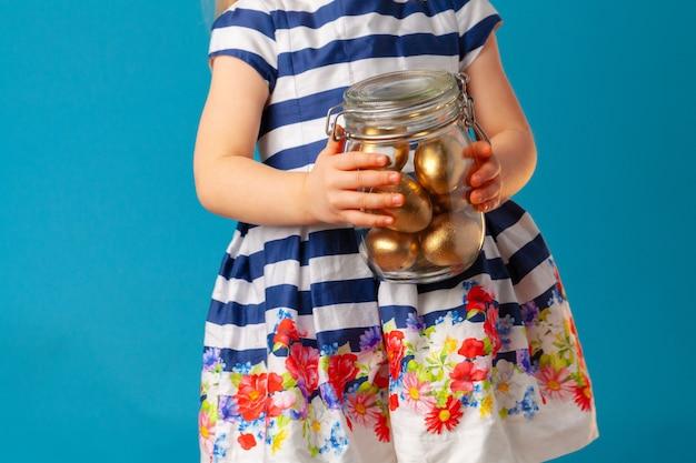 Kleines süßes mädchen, das glas mit goldenen eiern hält, die für ostern gefärbt werden