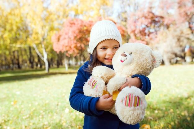 Kleines süßes mädchen, das großen teddybär hält