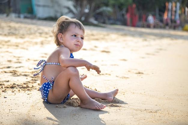 Kleines süßes mädchen, das im urlaub an einem strand in der nähe des meeres sitzt und spielt